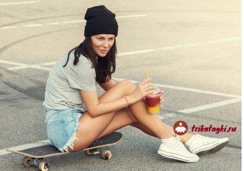 Девушка на скейте в джинсовых шортах и кроссовках