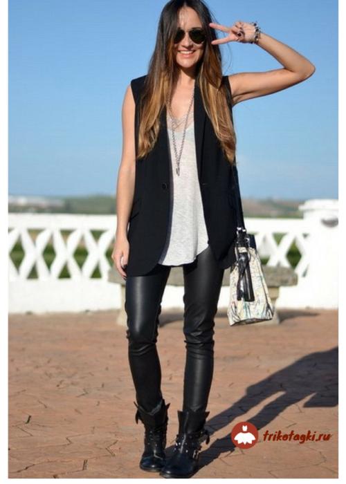 Женщина в кожаных брюках и кожаной жилетке в стиле рок