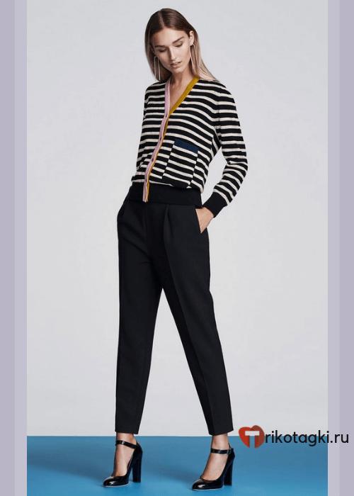 Девушка в черных брюках и кофте в полоску